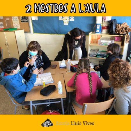 Dos mestres a l'aula ajuden a l'alumnat