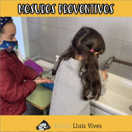 alumnes amb mascareta rentant-se les mans abans de dinar