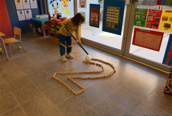 a kindergarten student traces the number 2